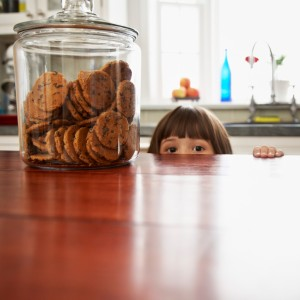 Girl Peeking Over the Counter at Cookies