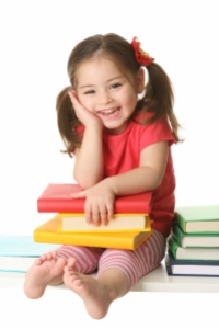 Young girl with books - How to Find Books in Spanish for Your Toddler - Alldonemonkey.com